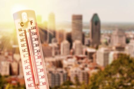 Thermometer in front of an urban skyline during heatwave