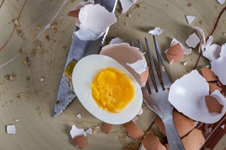 Sliced hard boiled eggs on plate with knife and fork