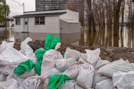 House submerged by water during floods, with sand bags in the foreground.