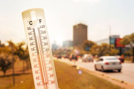 Thermometer in front of cars and traffic during heatwave in Montreal.