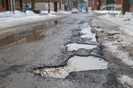 Large potholes in Montreal street, in Winter