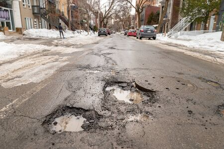 Montreal, CA - 13 March 2019: Large potholes in Montreal street, in Winter