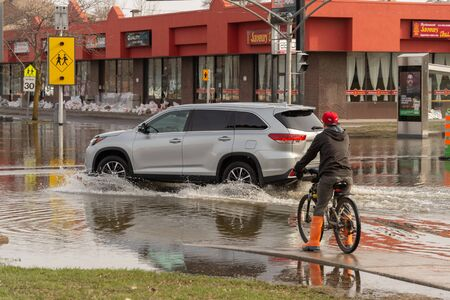 Pierrefonds-Roxboro, Quebec, Canada - 29 April 2019: car driving on a submerged street during spring floods