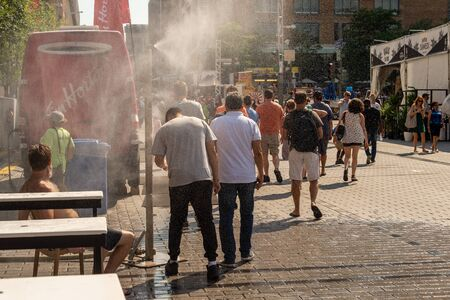 Montreal, CA - 27 July 2019: People walking under misting system to cool off (mist cooling system) during heatwave in Quartier des festivals.