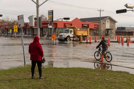 Pierrefonds-Roxboro, Quebec, Canada - 29 April 2019: People looking at a submerged street during spring floods