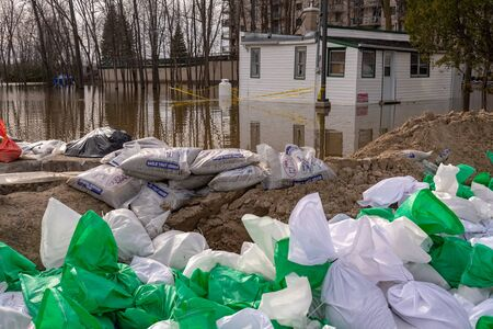 Pierrefonds-Roxboro, Quebec, Canada - 29 April 2019: house submerged by water during spring floods, with sand bags in the foreground.