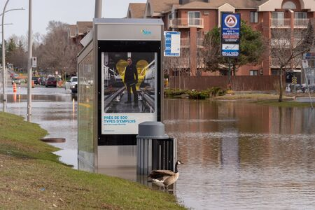 Pierrefonds-Roxboro, Quebec, Canada - 29 April 2019: submerged bus stop during spring floods