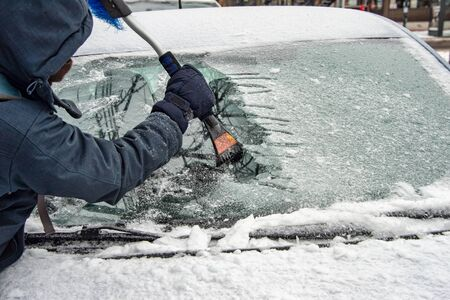 Man cleaning car windshield from ice with scraper tool.