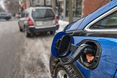 Electric car plugged in and charging in the wintertime (Montreal, Canada)
