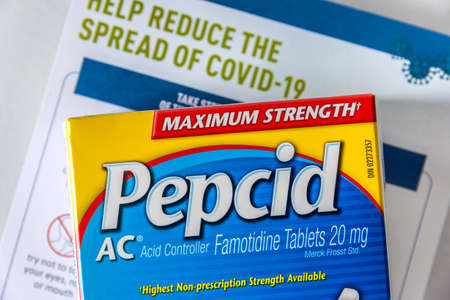 Montreal, CA - 27 April 2020: Box of Pepcid AC antacid medicine in front of a Covid-19 prevention document