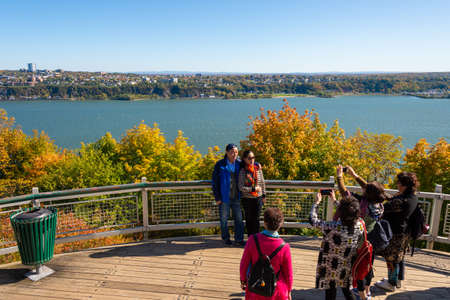 Quebec City, CA - 5 October 2019 - Tourists posing for pictures in front of Saint-Lawrence River and Levis City