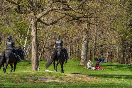 Montreal, Canada - 16 May 2020: Mounted Police patrol public parks to enforce the coronavirus physical-distancing laws in Mount Royal Park