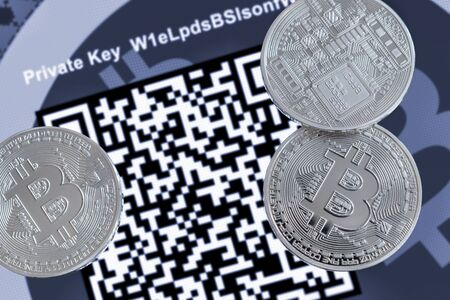 Cryptocurrency Bitcoin metallic coins, QR code and paper wallet. Фото со стока