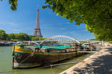 Paris, France - 23 June 2018: Residential barge on the Seine River with Eiffel Tower in background Éditoriale