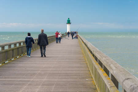 Calais, France - 19 June 2018: People walking on the west jetty in the summertime. Редакционное