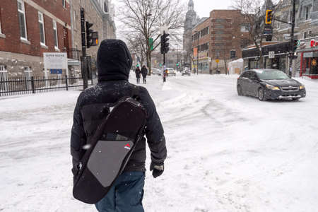 Montreal, Canada - 20 January 2019: Pedestrian walking on Mont-Royal Avenue during snow storm Редакционное