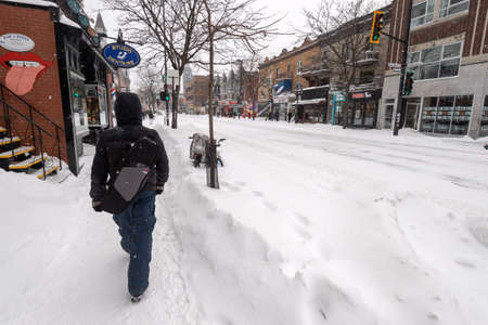Montreal, Canada - 20 January 2019Pedestrian walking on Mont-Royal Avenue during snow storm Редакционное