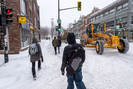 Montreal, Canada - 20 January 2019: Pedestrians walking on Mont-Royal Avenue during snow storm Редакционное