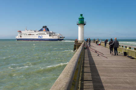 Calais, France - 19 June 2018: People on the west jetty and cross Channel P&O ferry leaving the port. Редакционное