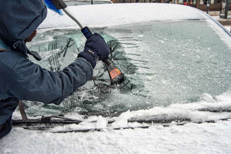 Montreal, Canada - 7 February 2019: man cleaning car windshield from ice with scraper tool.