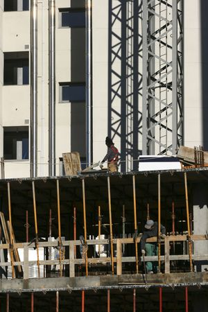 Two workers on different floors on a building under construction.