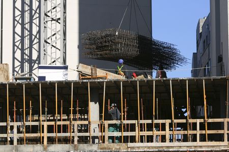 Some people and a crane working on a building under construction. Stock Photo