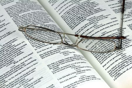 A pair of reading glasses and a book showing pages of Shakespeare%uFFFDs  Stock Photo