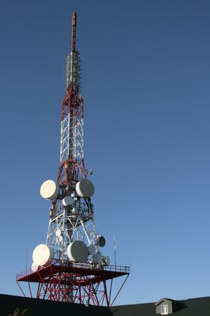 A telecommunications tower over a clean blue sky.