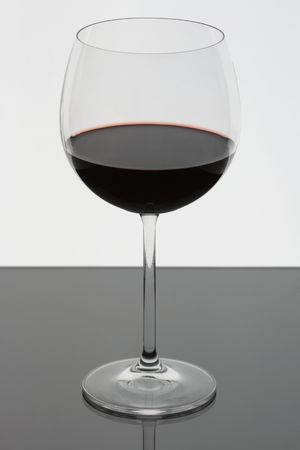 A glass of red wine on a reflective surface. Stock Photo