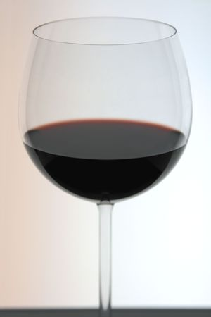 A backlit glass of red wine