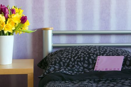 bed with a surprise letter and a vase with flowers photo
