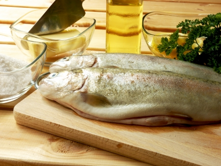 fish husbandry: Two fresh trout ready to cook, wooden cutting board, salt, butter, oil, lemon, chive leaves