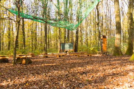 wide angle view on outdoor class room in forest with blank green chalk board, wooden school benches and book shelf in autumn with brown leaves on the ground Stock Photo