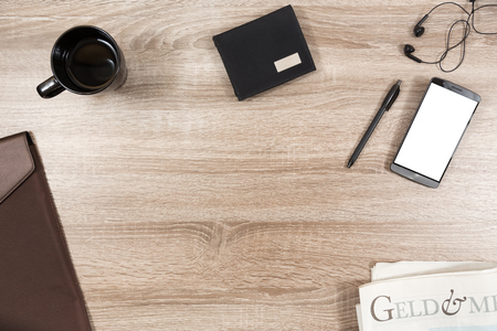top view on wooden desk with smartphone with empty copy space, black headphone earpieces and cables, a black pen, black coffee mug, brown briefcase, black wallet with blank metalic name tag and newspaper