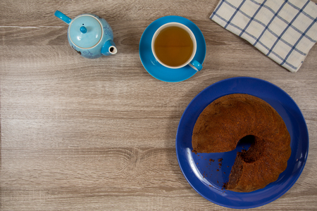 light blue cup and pot of tea with brown cake on deep blue plate on a wooden table 写真素材