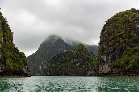 beautiful landscape of island mountain tops forming ha long bay in Vietnam in clouds