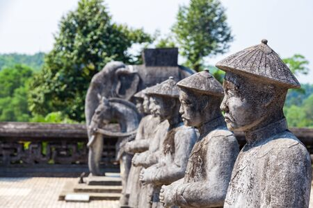 ancient stone statues of asian soldiers with weapons and in full armor in Vietnam