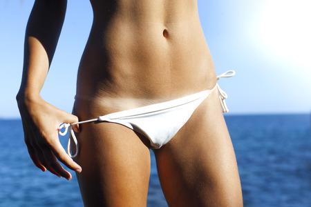 niñas en bikini: Mujer bronce carrocería bronceada en verano con la línea del bikini