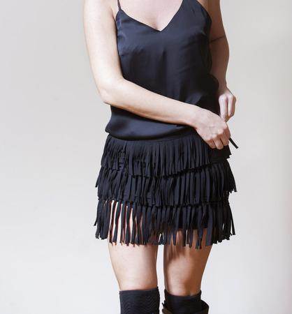 stuck up: Woman in black silk shirtstriped skirt and wool stockingsclosing zipper