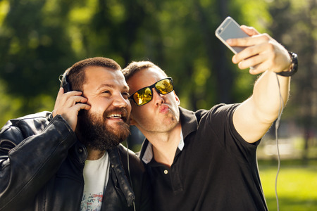 funny guys: Two friends taking a selfie photo with mobile smart phone in nature, listening to music with headphones