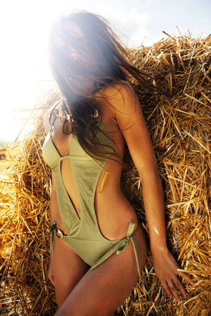 flare stack: Sexy woman in swimming suit nex to the hay stack with sun flare Stock Photo