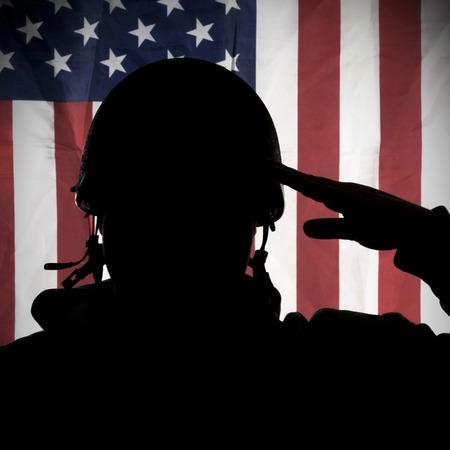 estrellas  de militares: Americana EE.UU. soldado saludando a la bandera EE.UU. Foto de archivo