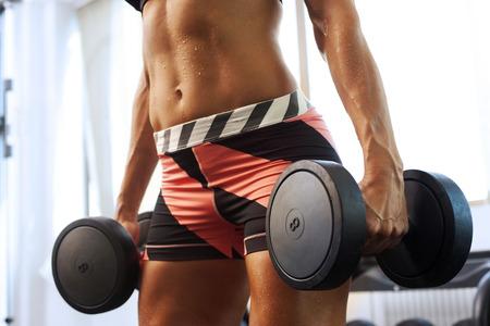 Mujer hermosa joven con los músculos levantando pesas que muestran los músculos del abdomen