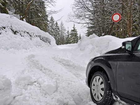 A car in the mountains with lots of snow and a closed street photo