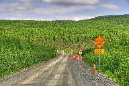 one lane street sign: Single lane bridge in the wilderness of alaska