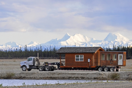relocate: House on a truck with the mountains of the Alaska Range in the Background Editorial