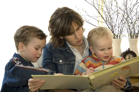 A young mother reading a book for her two sons.