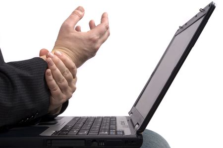 A business man holding his hands because of pain while working on a laptop.
