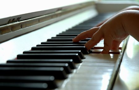 dof: The hand of a 4 year old playing the piano with a nice DOF. Stock Photo