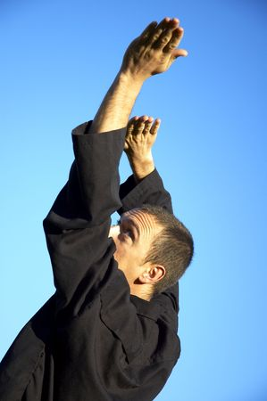 a man in a pencak silat pose on a sunny day with blue background. Stock Photo - 388620